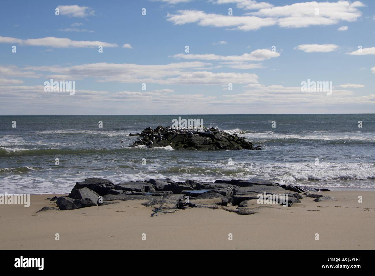 Daytime stock photo of rocks off the shoreline of beach in Spring Lake, New Jersey on sunny morning. - Stock Image