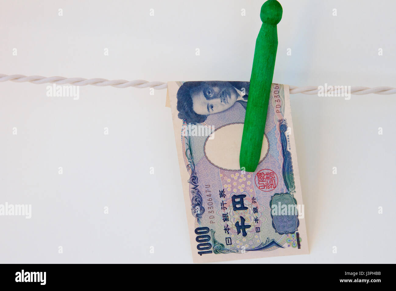 Japanese yen hanging on a line with a peg. - Stock Image