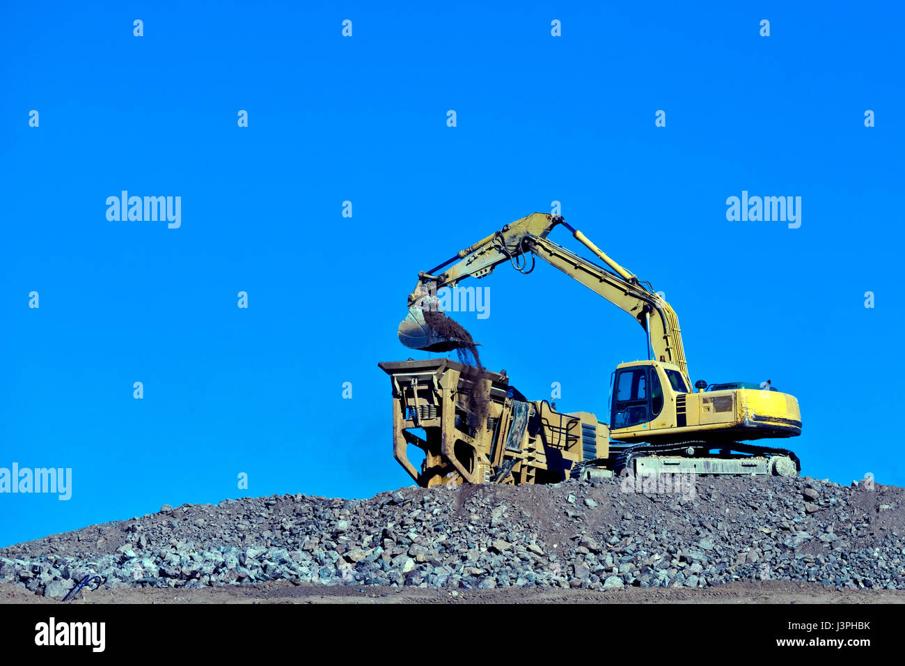 Earth moving equipment loading soil into waiting container - Stock Image