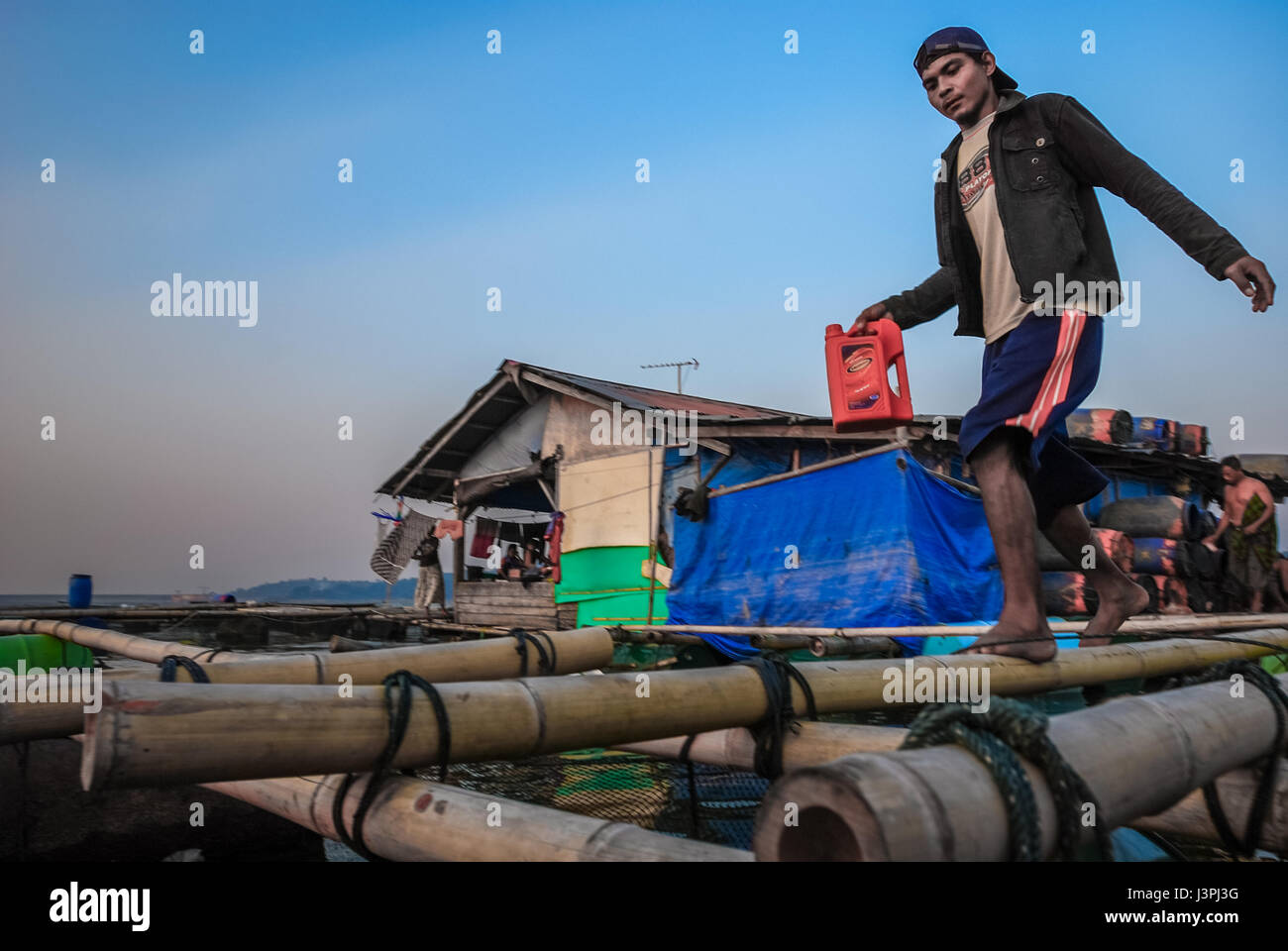 A boat motorist carries a plastic oil can while stepping on bamboo platform in the floating village of Jatiluhur - Stock Image