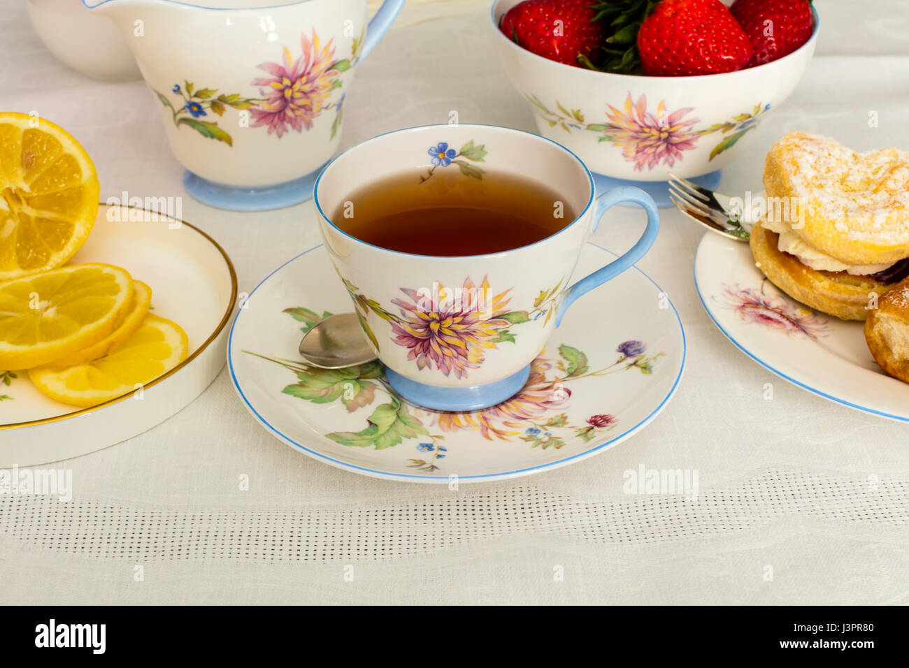 Cup of tea served in a vintage fine china tea cup with fresh cream cakes. - Stock Image