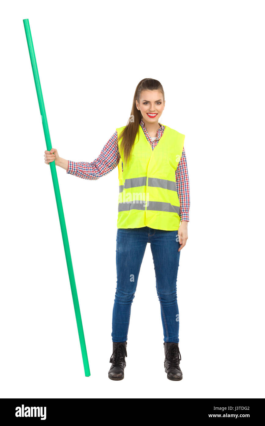 Young woman in yellow reflective vest, jeans, and lumberjack shirt standing legs apart and holding chroma key stick. - Stock Image