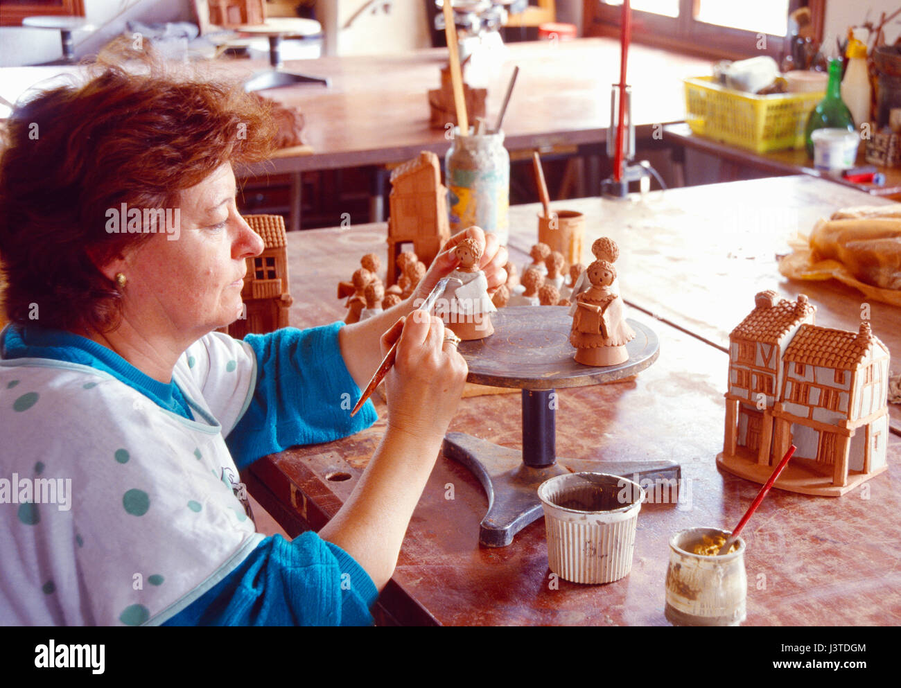Ceramist painting clay figures. - Stock Image