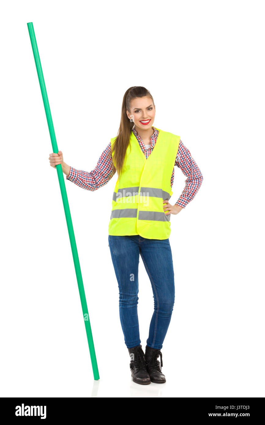 Young woman in yellow reflective vest, jeans, and lumberjack shirt posing with hand on hip and holding chroma key - Stock Image