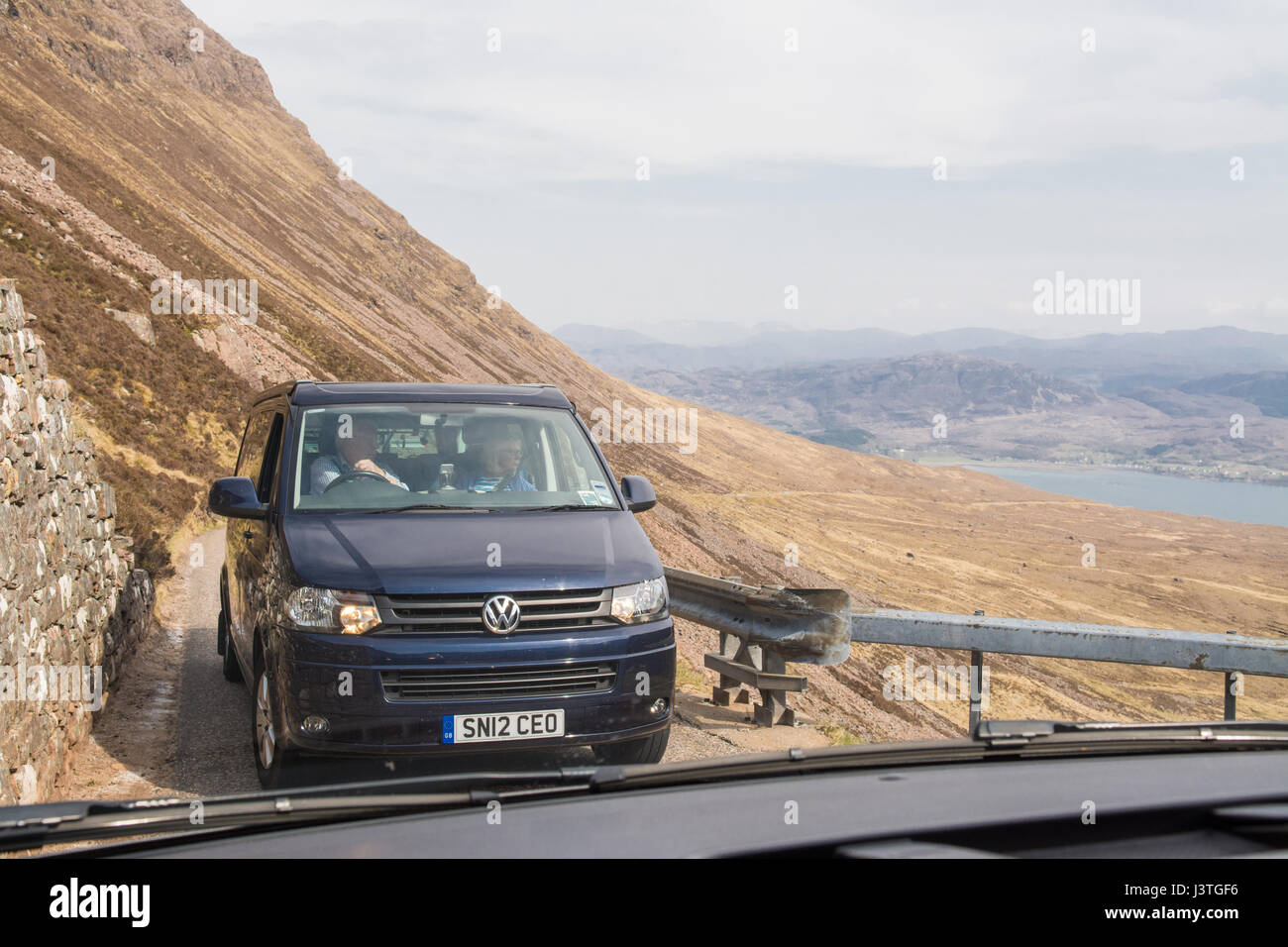 Bealach na Ba - camper van using passing place - viewed through windscreen of oncoming vehicle, Scottish Highlands, - Stock Image