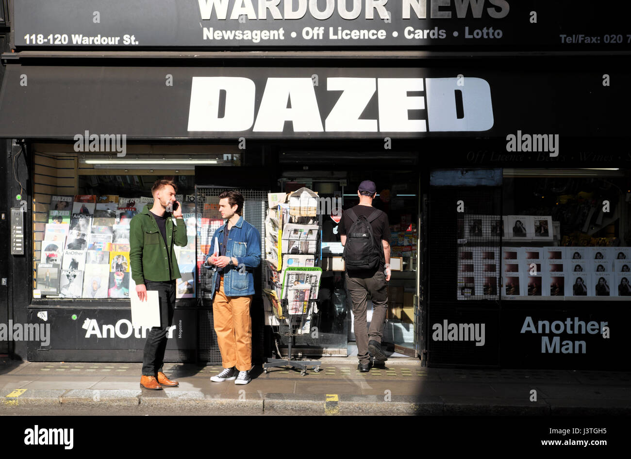Man and friend talking on mobile phone outside Wardour News newsagent shop with DAZED magazine sign in Wardour Street - Stock Image