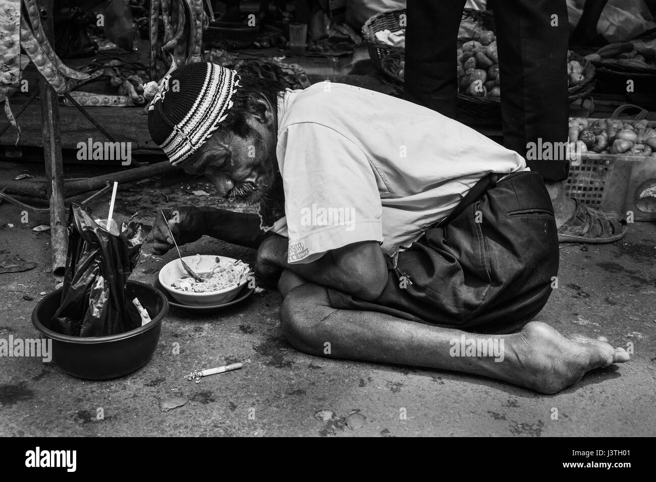 black and white portrait of a poor disabled old man eating noodles on a ground on a market in Sumatra - Stock Image