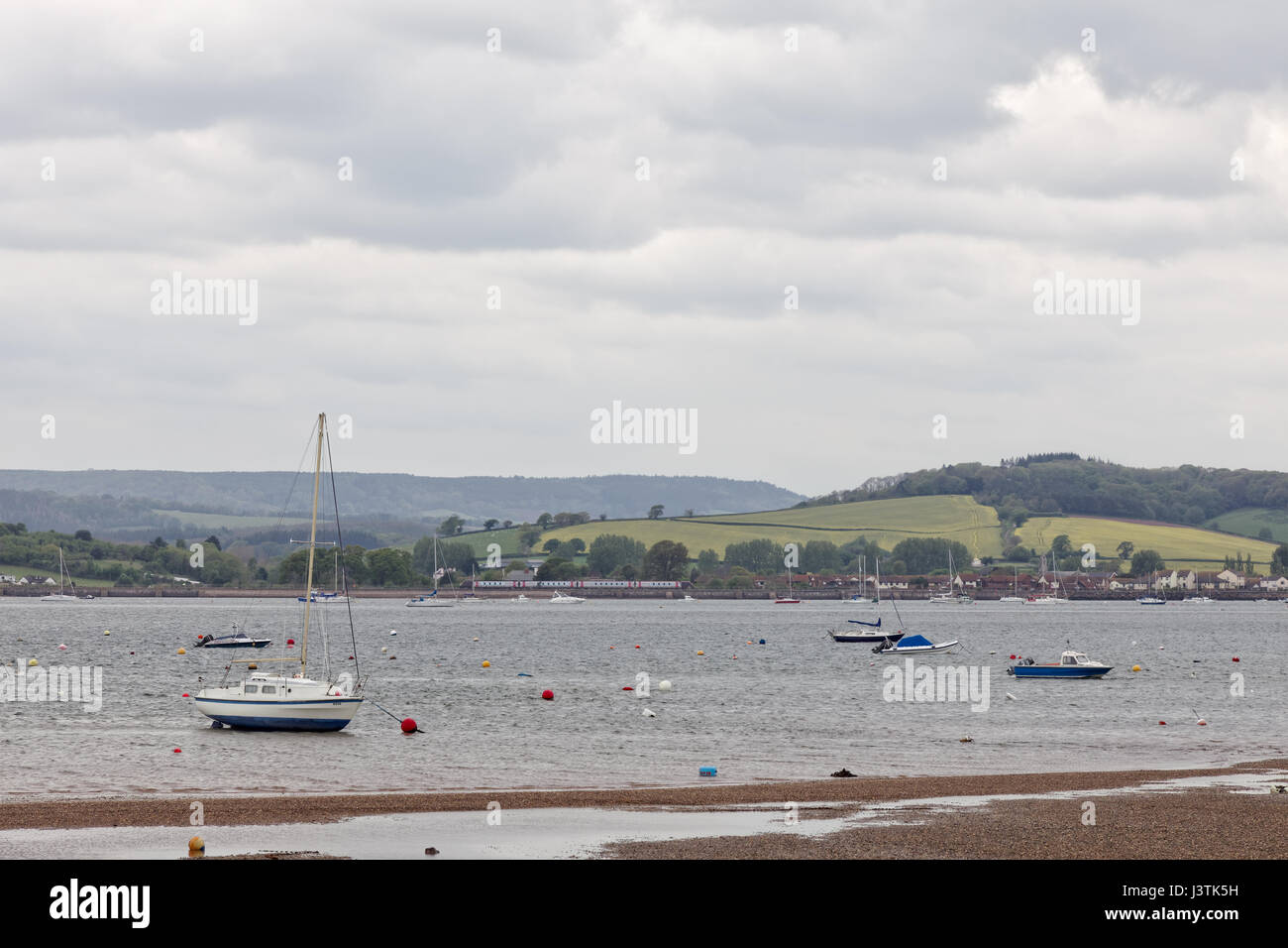 Boats moored in the River Exe estuary at Exmouth with Cross Country train on the Riviera line in the background - Stock Image