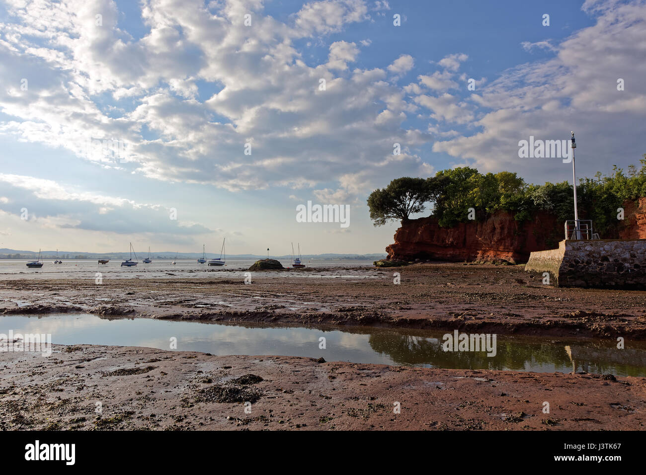 Wotton Brook flows into the River Exe estuary at low tide past the Lympstone boat shelter wall - Stock Image