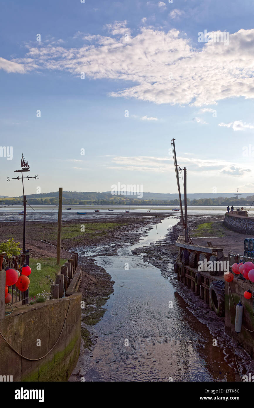 The Wotton Brook flows through Lympstone & enters the River Exe estuary at low tide - 2 figures on harbour wall - Stock Image