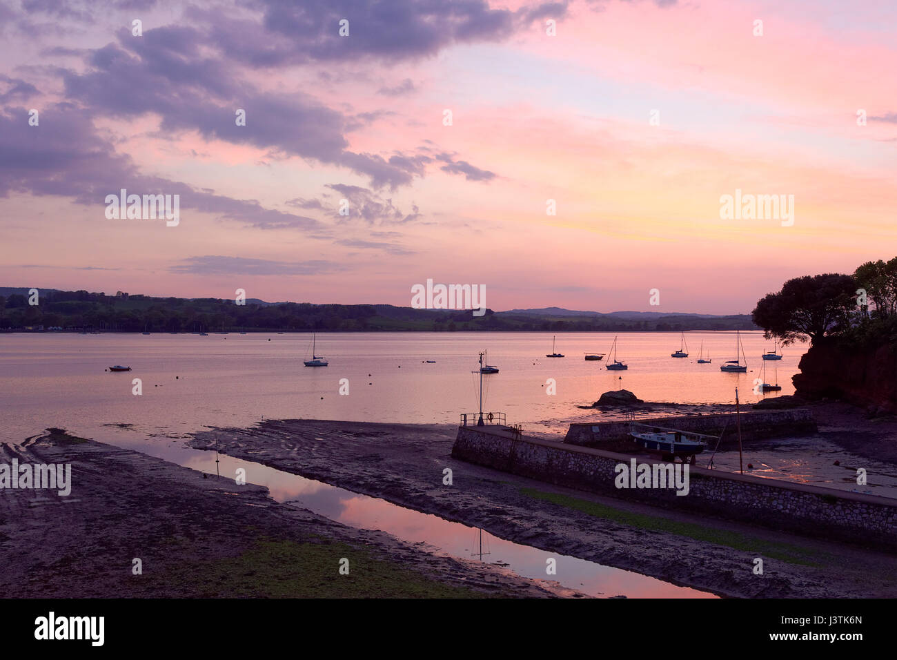 Sunset over the River Exe estuary seen from Lympstone towards Starcross & figure on harbour wall - Stock Image