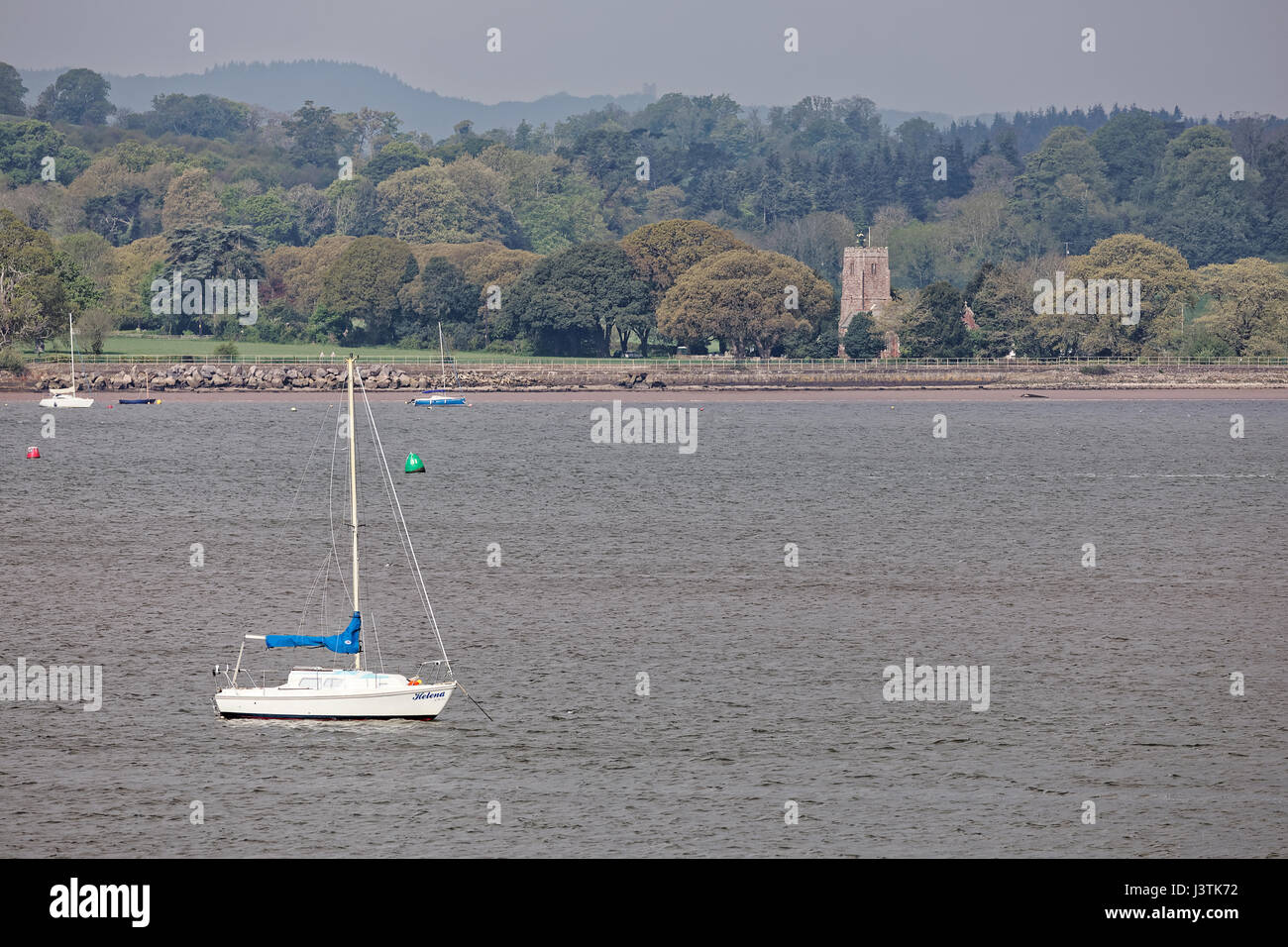 Sailing boats moored in the River Exe estuary with Powderham Church of St Clements in the background - Stock Image