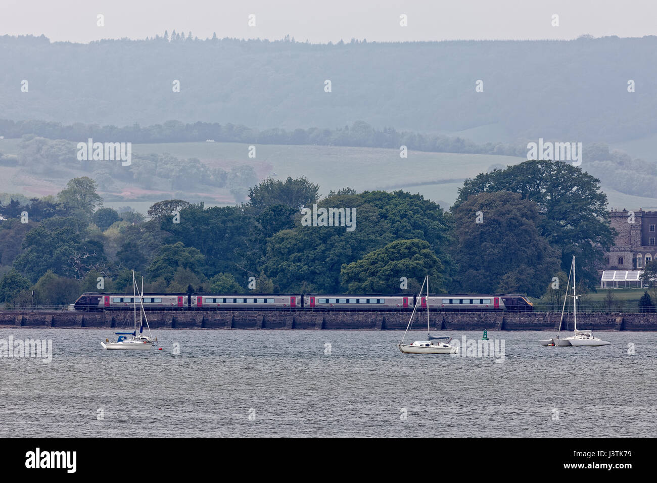 Cross Country intercity train on the Riviera Line moving left to right adjacent to River Exe close to Powderham - Stock Image