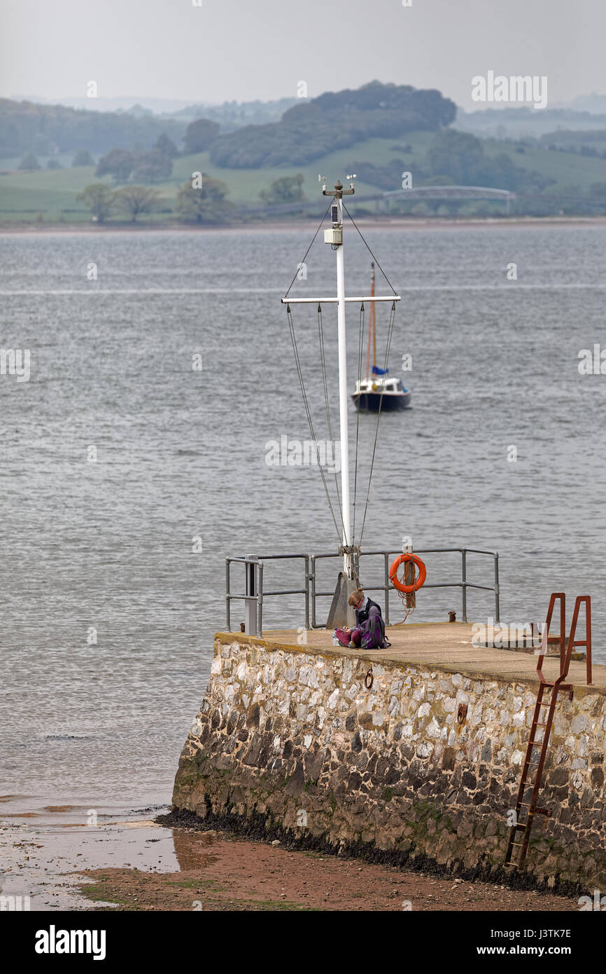 Woman using mobile phone while sat on Lympstone harbour wall - Stock Image