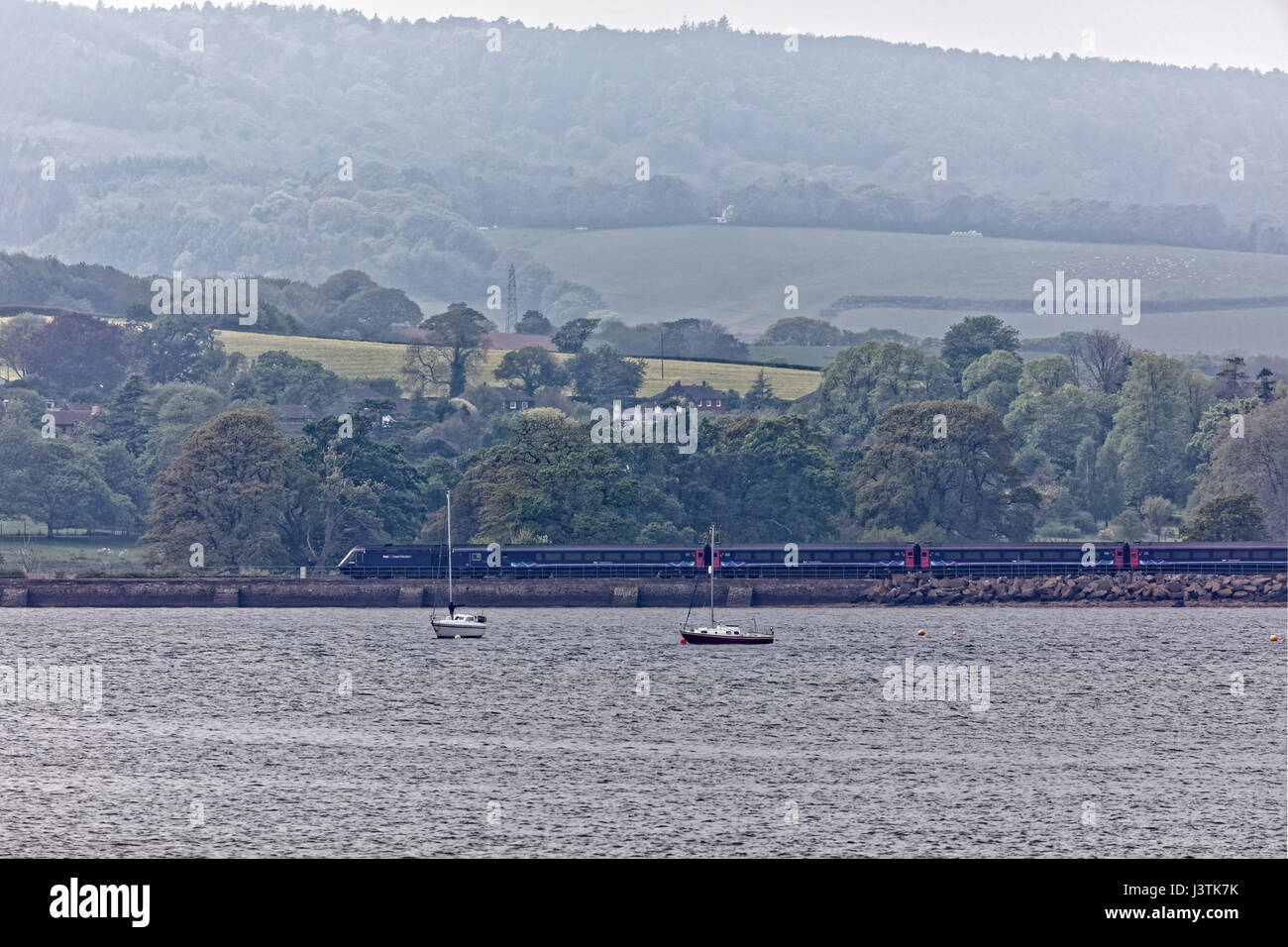 First Great Western intercity train on the Riviera Line adjacent to the River Exe - moving right to left. - Stock Image