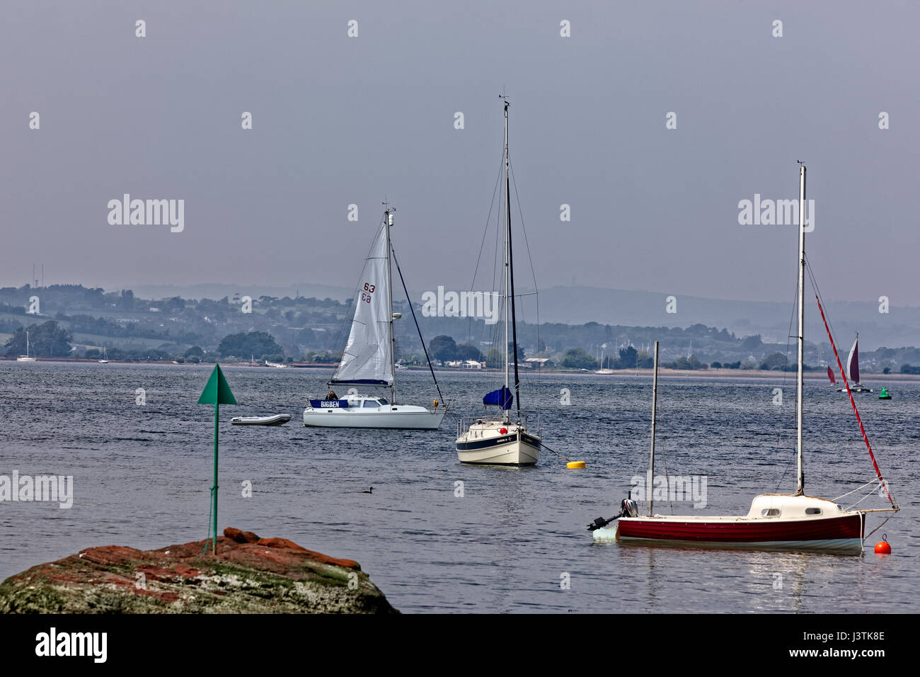 Sailing boats on the Exe estuary - a crewman prepares to get underway - navigation warning in foreground - Stock Image