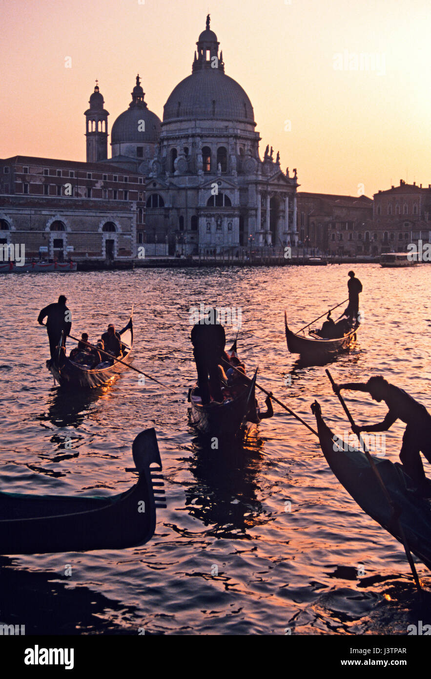 Venice a view across the lagoon to the church of Santa Maria della Saute in the evening sunset light  with Gondolas - Stock Image