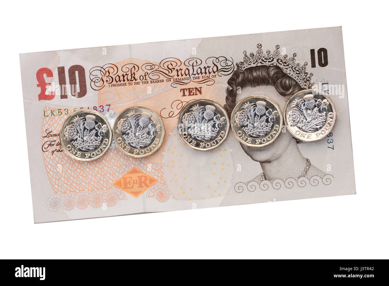 New pound coins across a £10 pound note, UK. - Stock Image