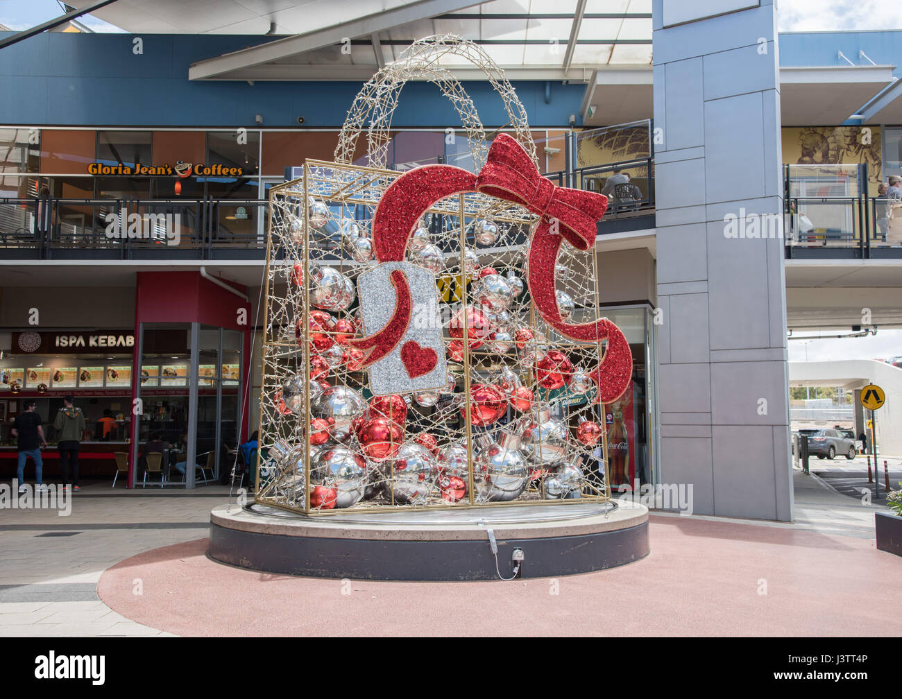 Large metallic silver and red package with ornaments and bow to celebrate Christmastime near urban shopping mall - Stock Image