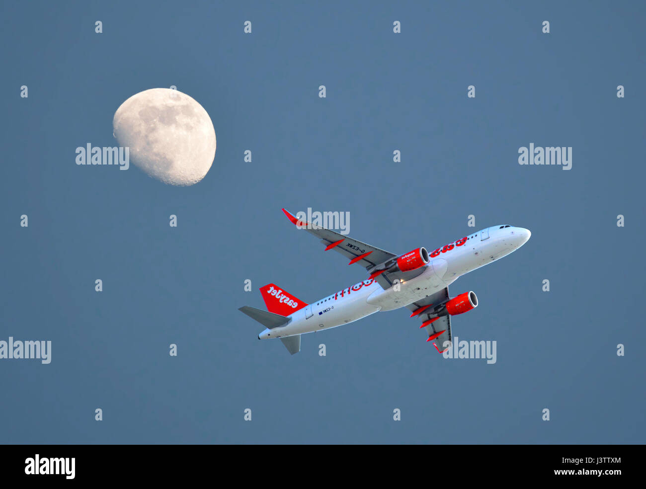 Easyjet Airbus A320 aircraft taking off from Faro Airport with a three quarter moon in the evening sky - Stock Image