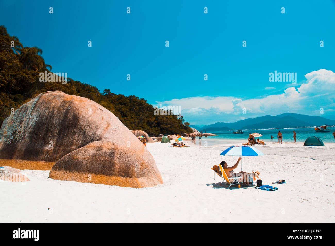 sunbathing tourist at the beach of ilha do campeche, Florianópolis - SC - br - Stock Image