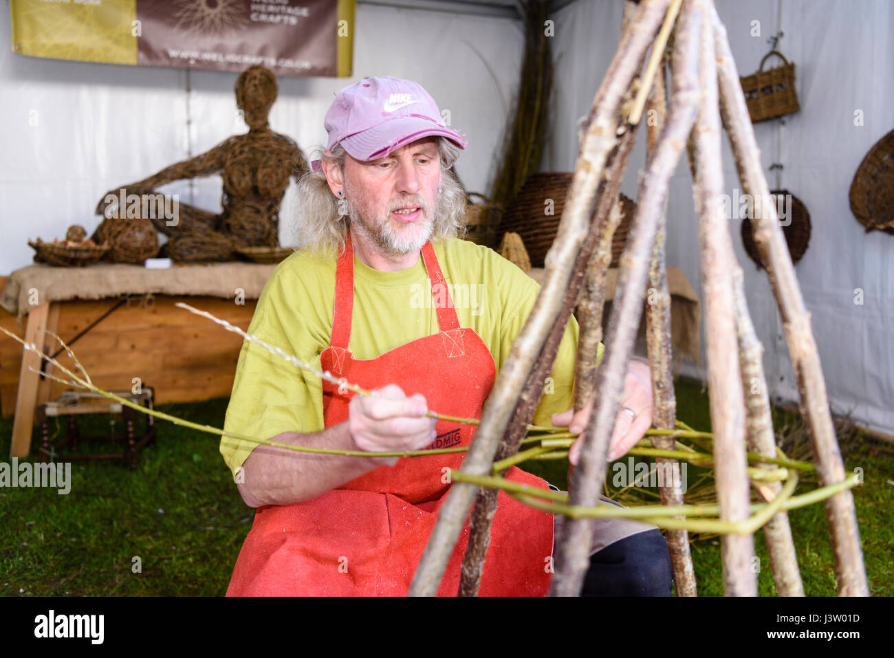 A male weaver begins weaving willow around a wooden frame - Stock Image