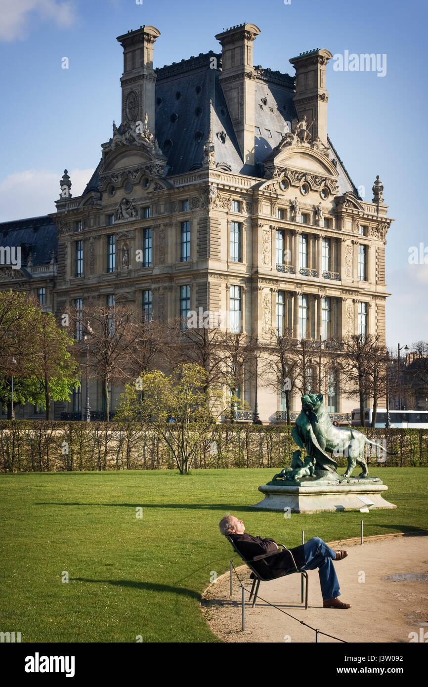 Tourist is relaxing on a bench In the park in front of the Louvre. View from Avenue du General Lemonnier to Jardin - Stock Image