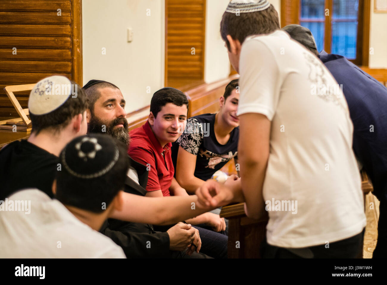 Boys talk to Rabbi after Mincha prayer service in the Six-domed Synagogue in Qırmızı Qəsəbə, or Red Town, Quba district - Stock Image
