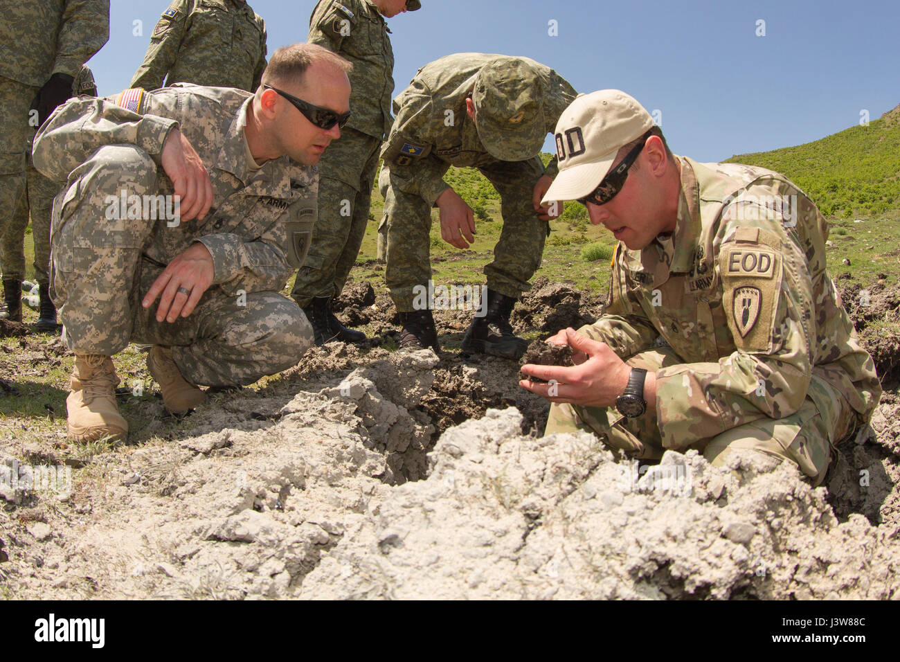 us army staff sgt brian miller an explosive ordnance disposal team leader assigned to multinational battle group east inspects the remains of a shot