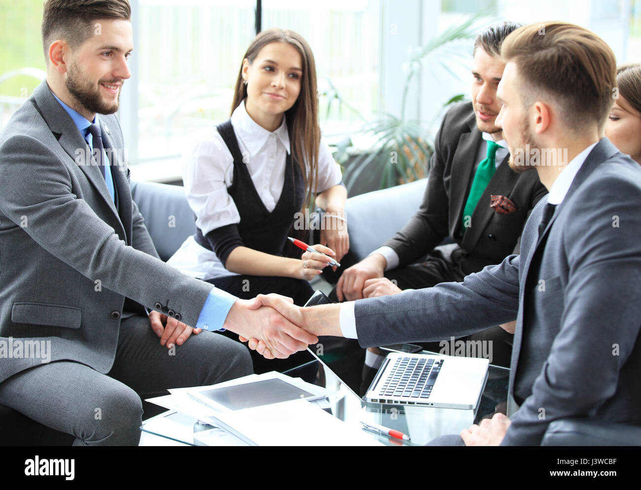 Business people shaking hands, finishing up a meeting. - Stock Image