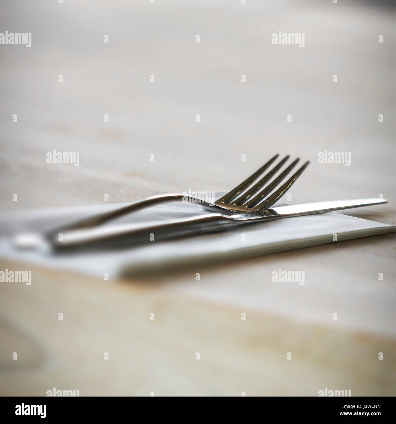 A knife and fork with a napkin Place setting Restaurant Unused - Stock Image