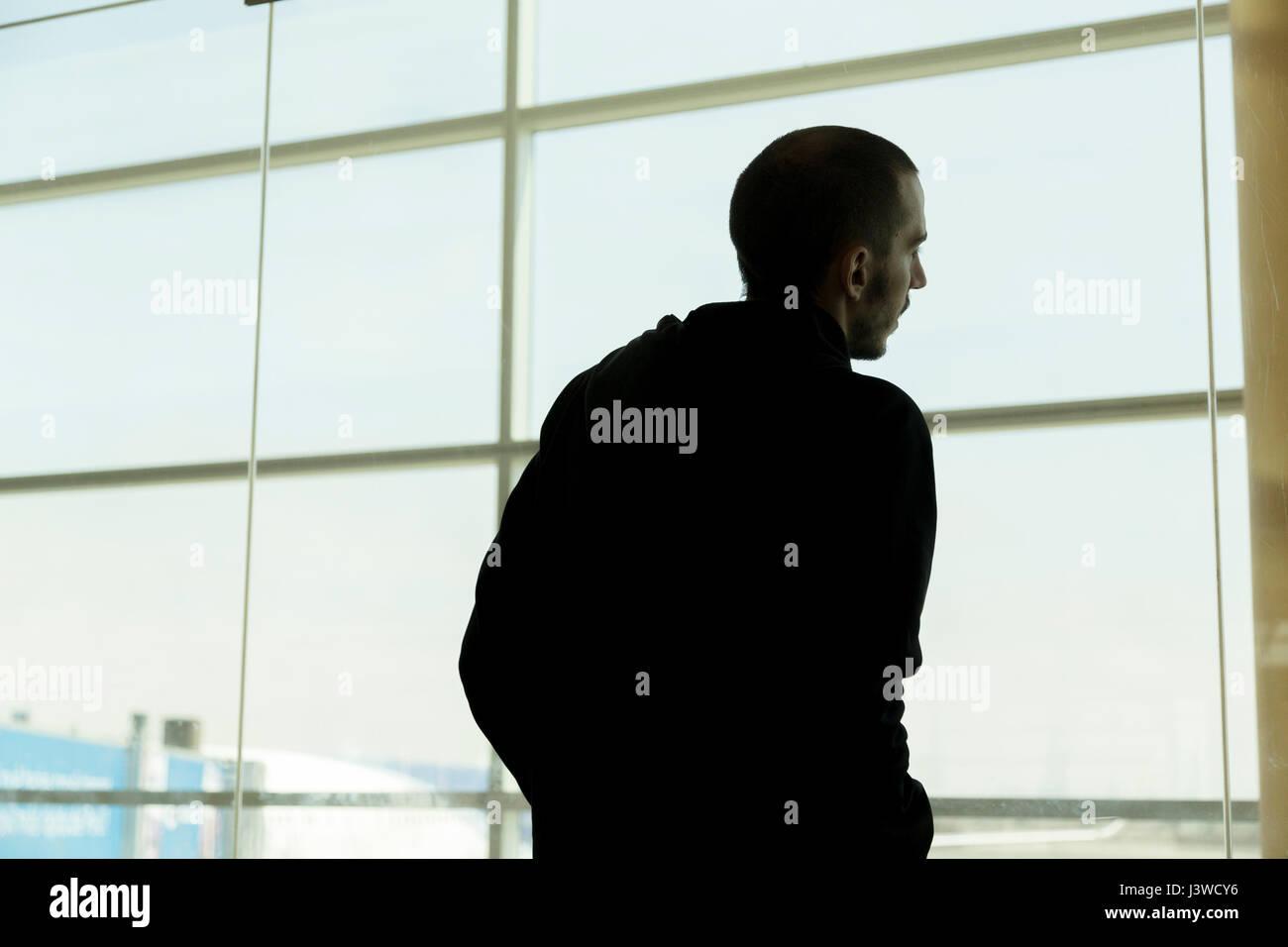 Man looking through window - Stock Image