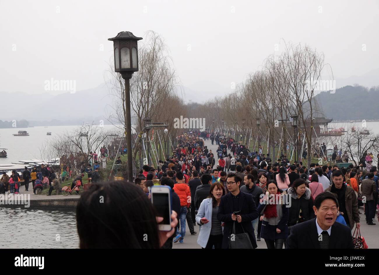Crowd Of Tourists And Boatmen On West Lake Coast Famous Park In Hangzhou City