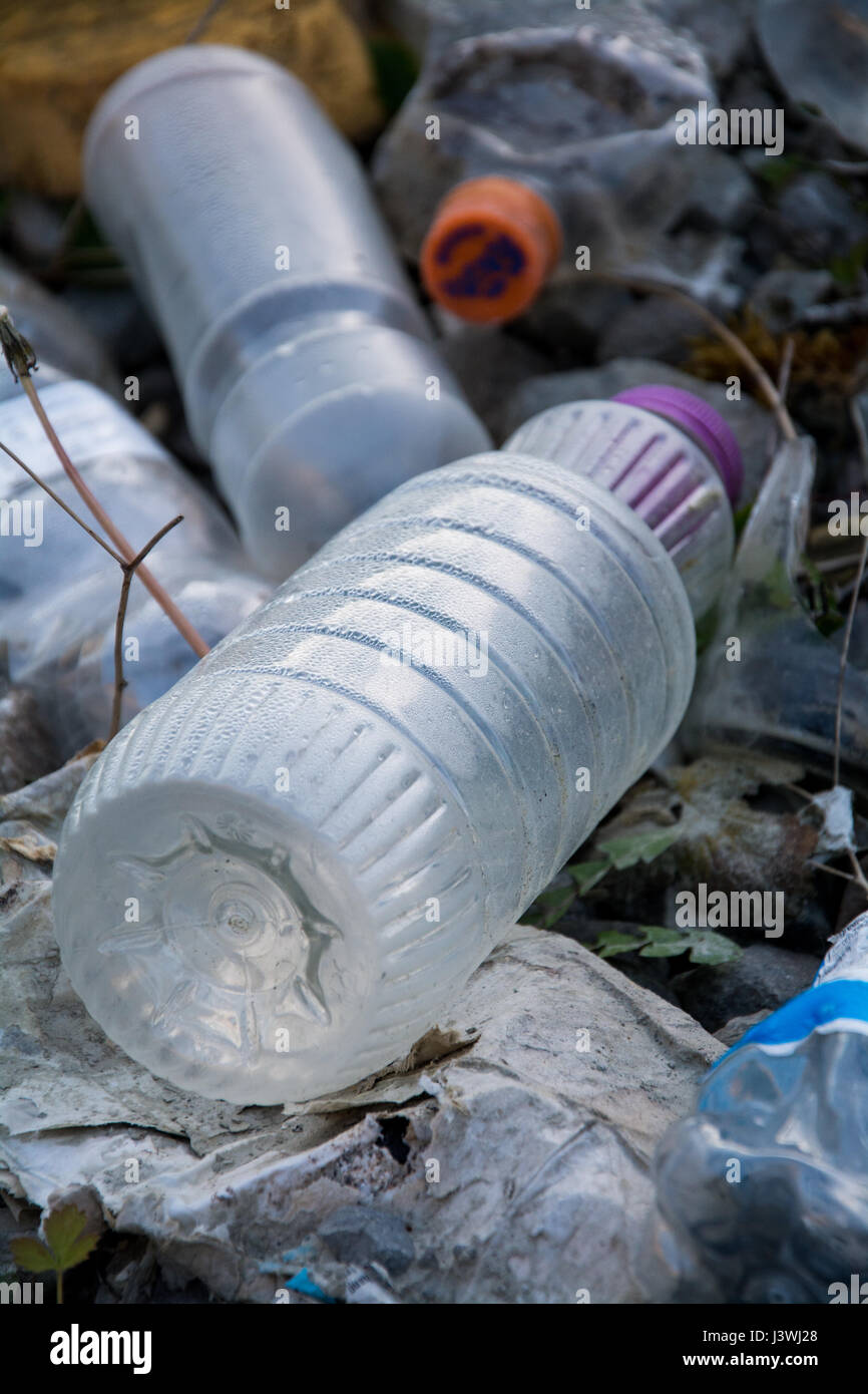 An image of rubbish that's been fly tipped, with the focus on an empty drinks bottle. It represents environmental - Stock Image