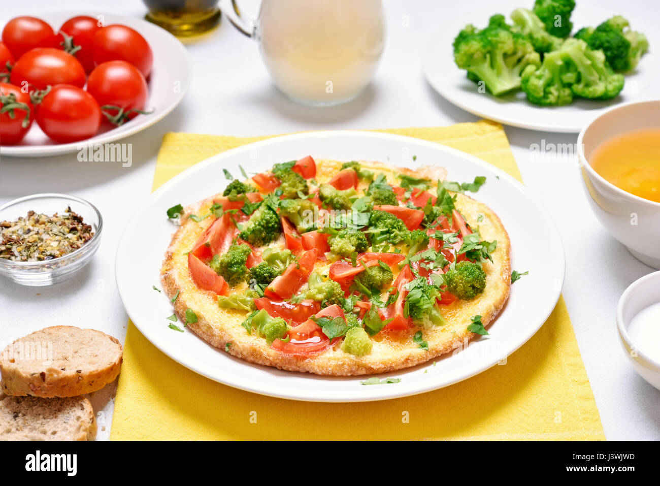 Breakfast with fried eggs. Omelet with vegetables on plate - Stock Image