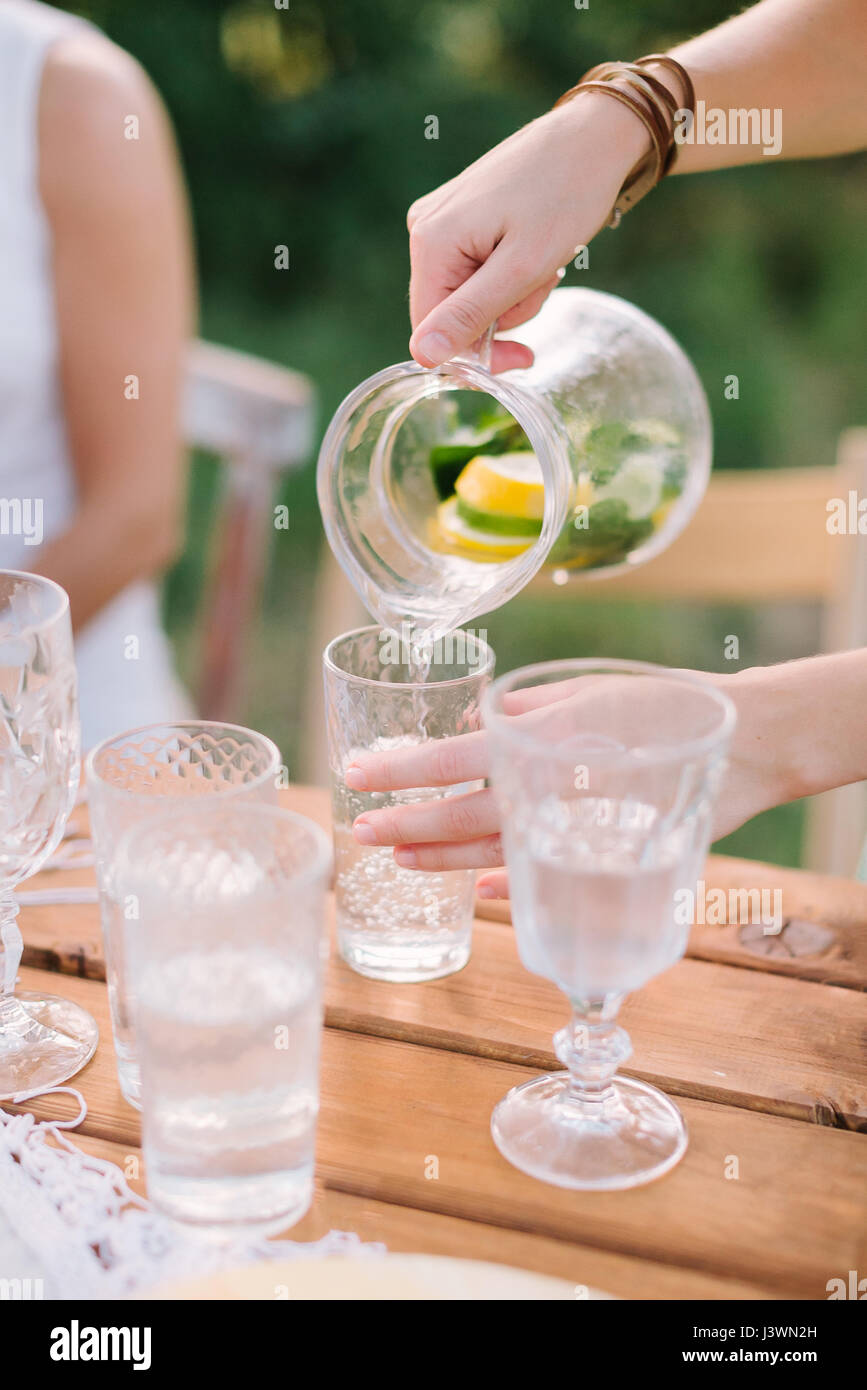 picnic, people, summer, holiday concept - female hands pouring lemonade from the decanter into a glass beaker, a Stock Photo