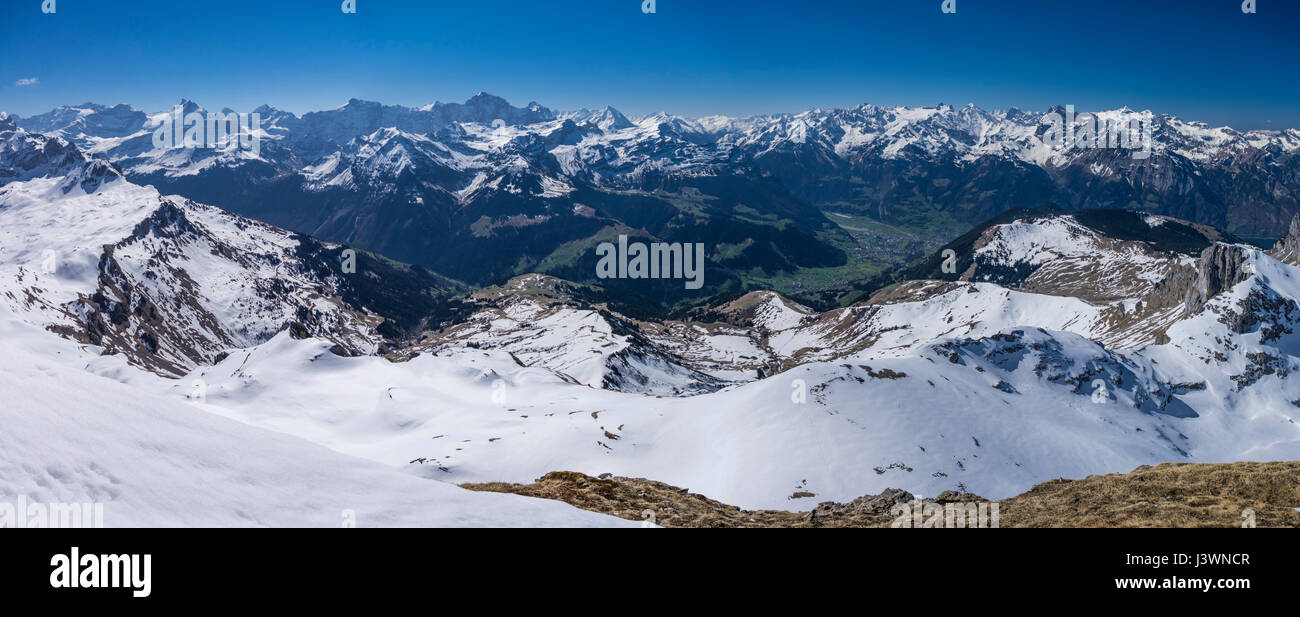 Panorama of snow-covered peaks and green valleys in the Swiss Alps, seen from Rossstock (2461m) in Southern direction. - Stock Image