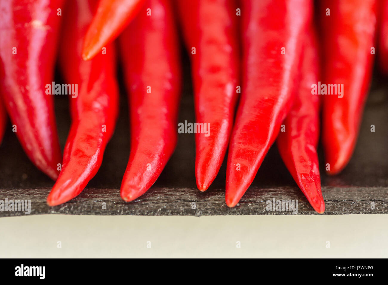 red hot chili peppers, popular spices concept - macro sharp tips of the red chili peppers, fresh clean juicy pods - Stock Image