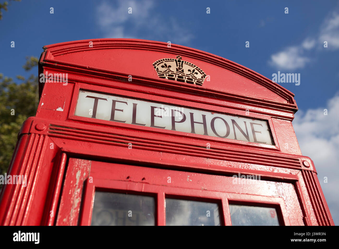 Top of traditional red telephone box in front of blue sky and trees. - Stock Image