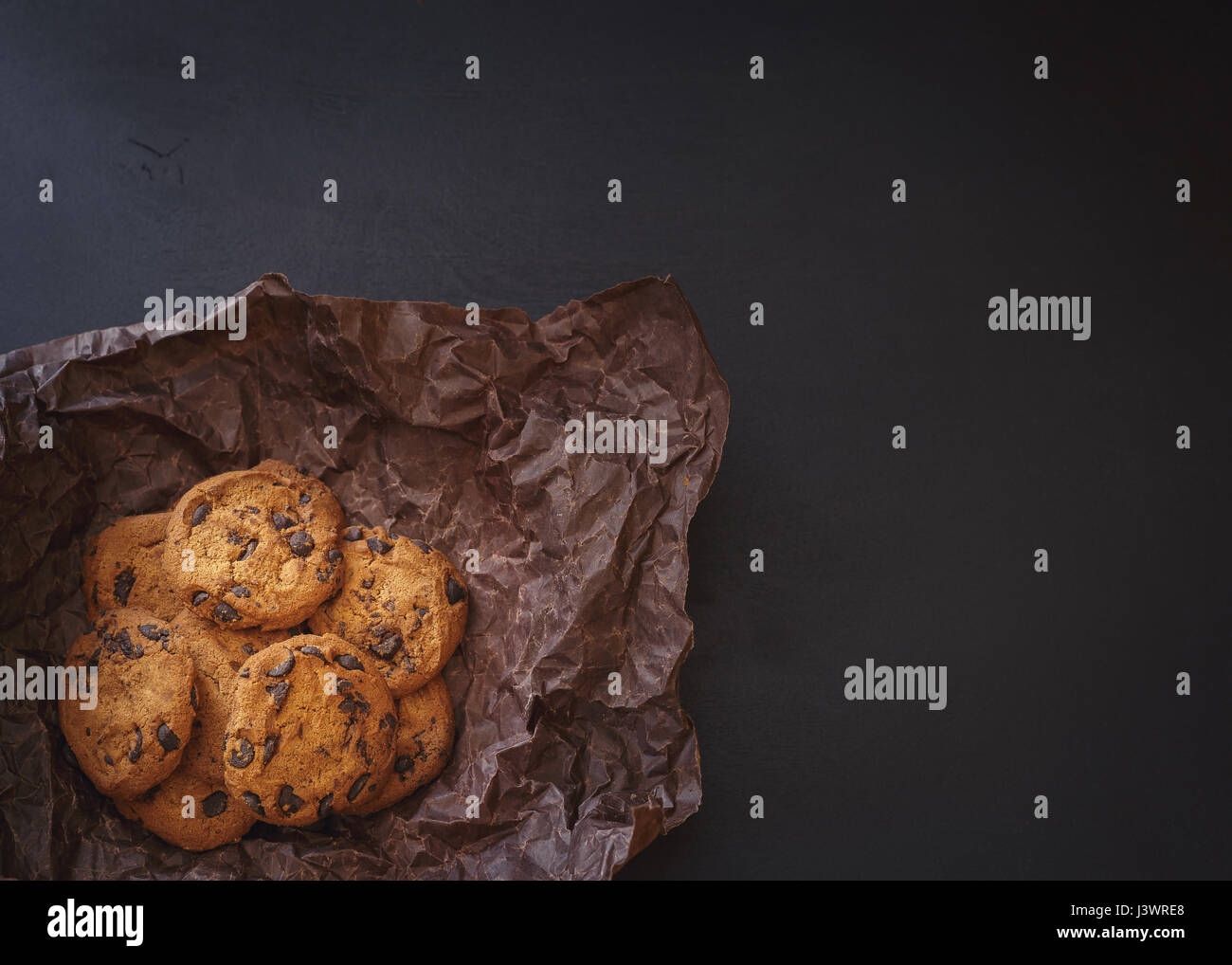 Chocolate chip cookies on crumpled paper over dark background in low light - Stock Image