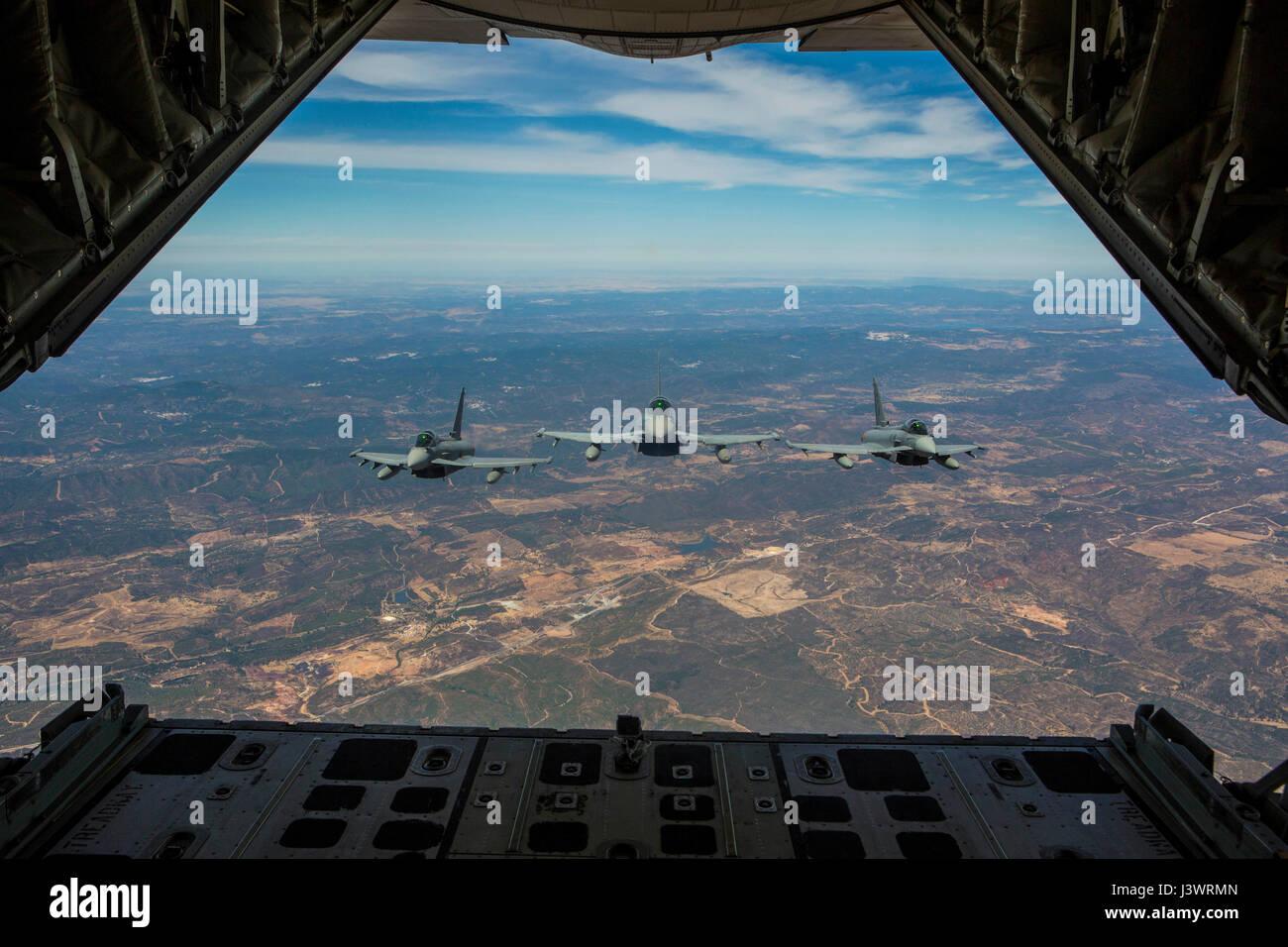 Three Spanish Air Force Eurofighter Typhoon combat aircraft escort a USMC KC-130J Hercules tactical aircraft during - Stock Image
