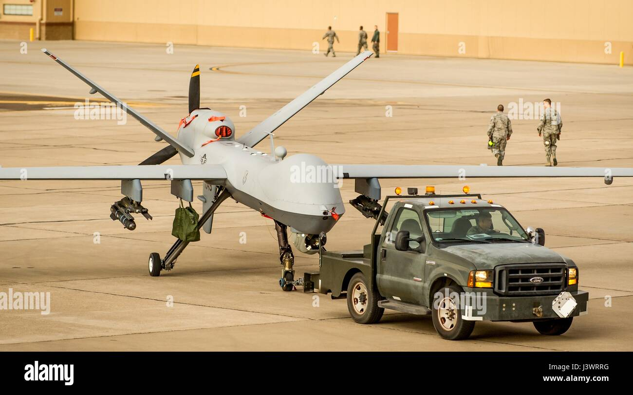 U.S. soldiers tow a USAF MQ-9 Reaper unmanned aerial vehicle aircraft from the runway at the Holloman Air Force - Stock Image