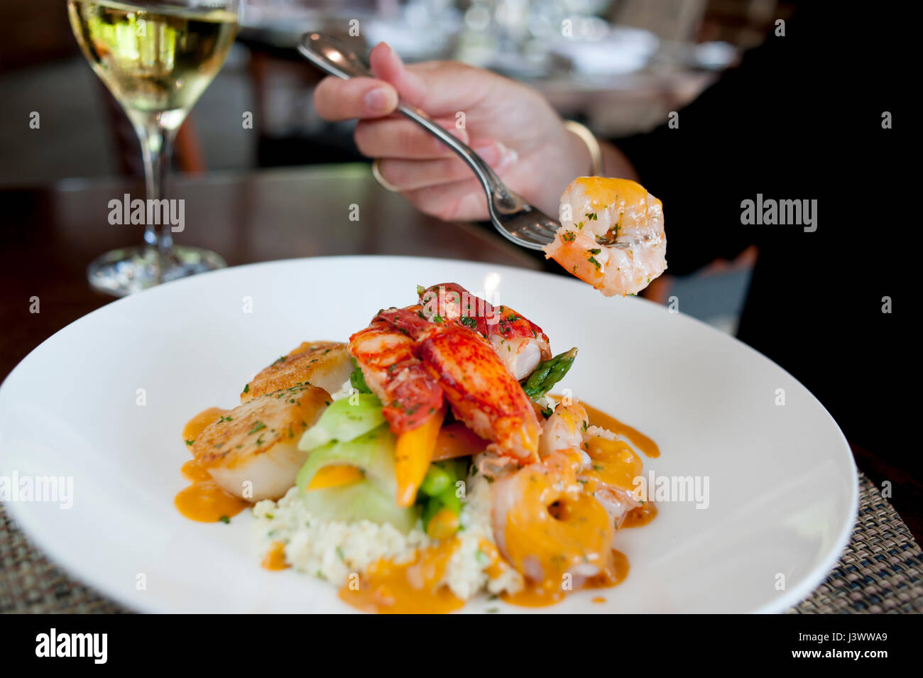 USA Food shellfish and grits at the Waypoint Seafood and Grill woman dining Williamsburg Virginia VA - Stock Image