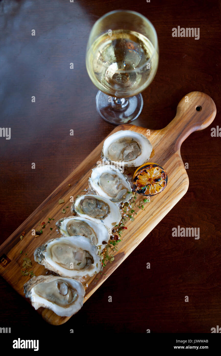 Food Raw oysters on a half shell with a glass of white wine with herbed salt sprinkled on the oysters Williamsburg - Stock Image