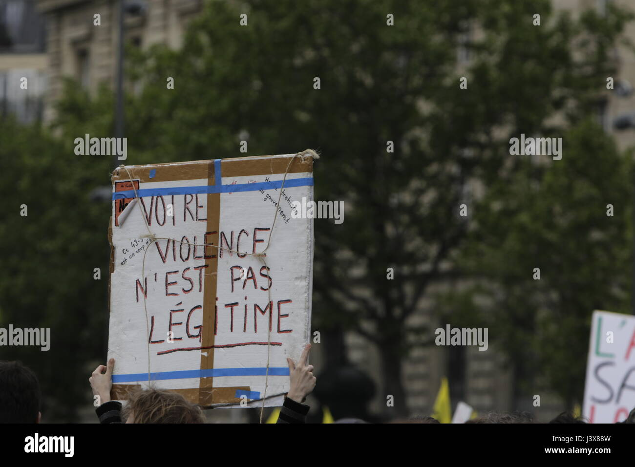 Paris, France. 8th May, 2017. A protester holds up a sign that reads 'Your violence is not legitimate'. - Stock Image