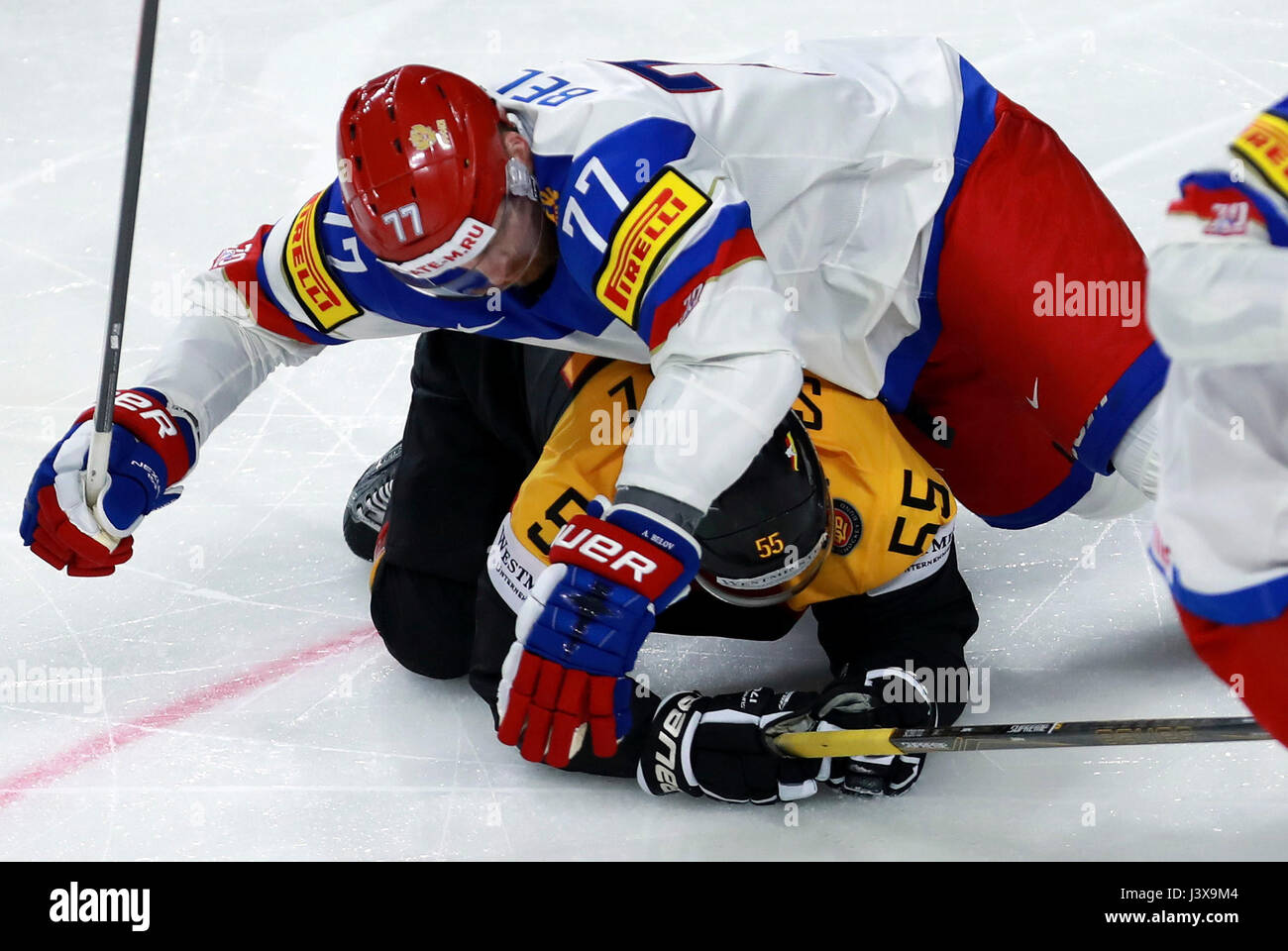 Cologne. 8th May, 2017. Anton Belov (Top) of Russia vies with Felix Schutz of Germany during the 2017 IIHF Ice Hockey Stock Photo
