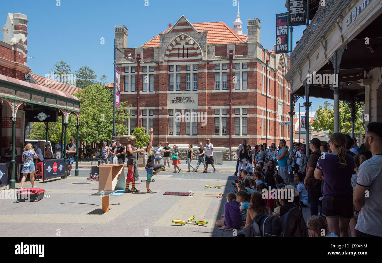 Fremantle,WA,Australia-November 13,2016:Buskers with crowd, Fremantle Markets and Fremantle Technical School building - Stock Image