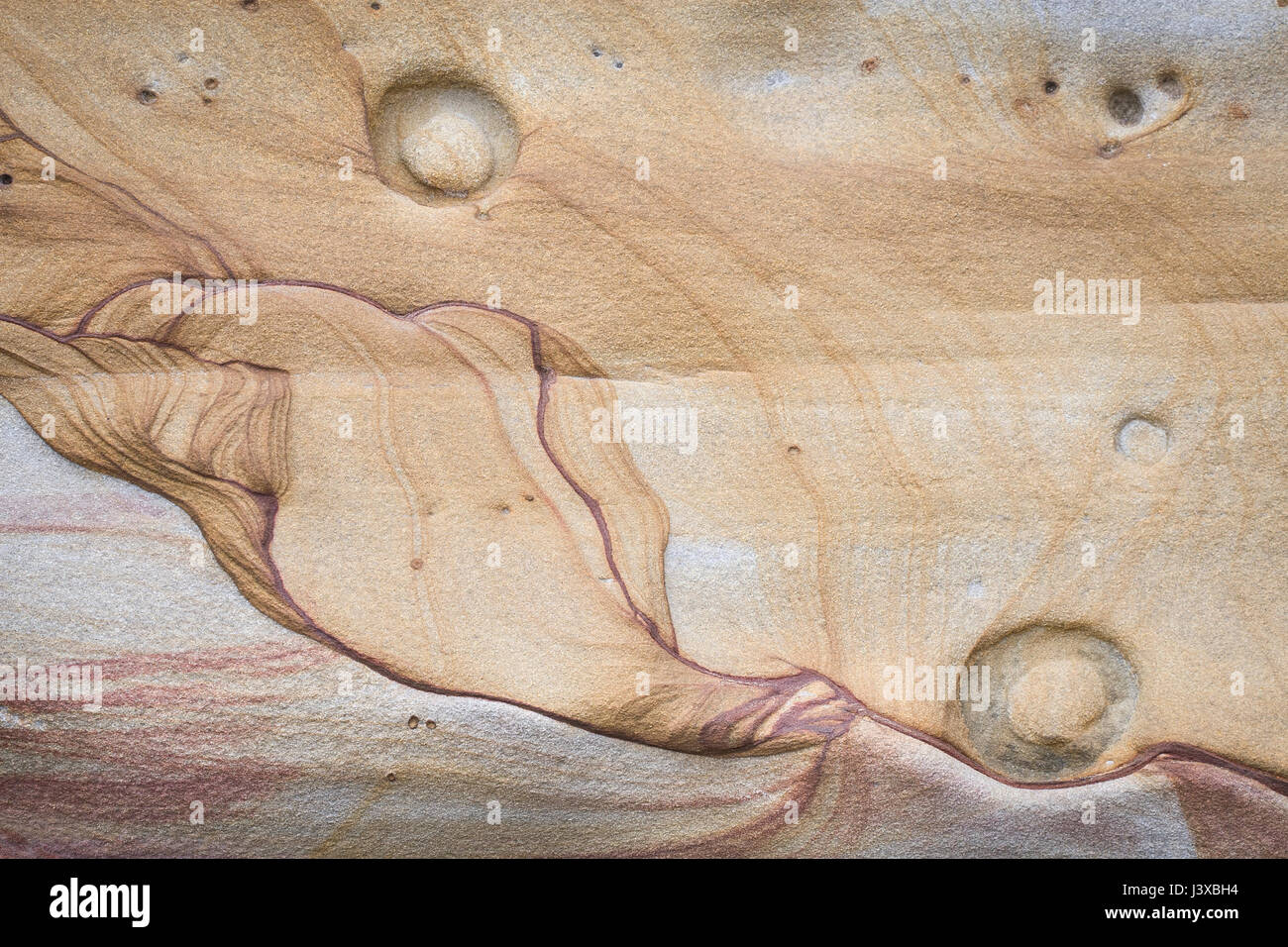 An abstract shape in a sandstone cliff that resembles a seated figure. Stock Photo