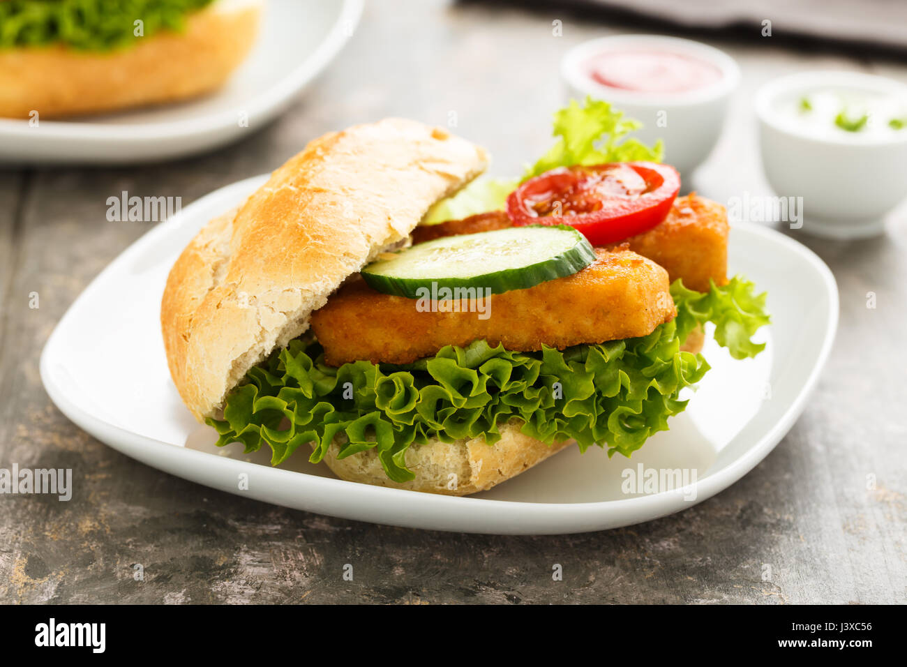Hearty fish fillet sandwich with salad and veggies. - Stock Image