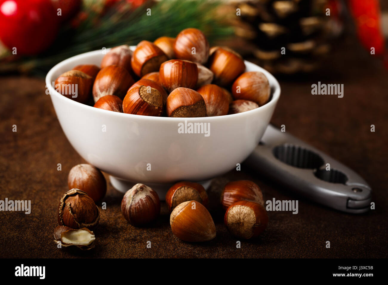 fresh hazelnuts served in a white bowl - Stock Image